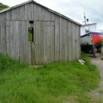 Rotting shed and beached boat