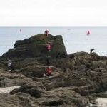 Scramblers on the rocks at Looe beach