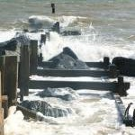 Waves break over a groyne near Waxham